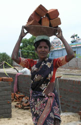 Image of an Indian woman carrying bricks to help rebuild schools