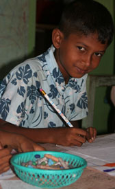 Image of a child drawing while attending a Child Centered Space in Hambantota