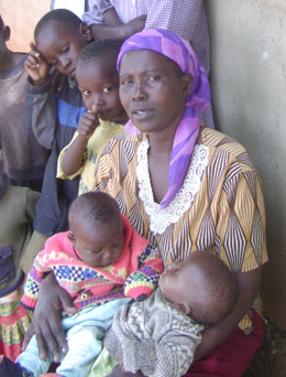 Image of John's wife, Jane, with her children after fleeing from Kenya to Uganda
