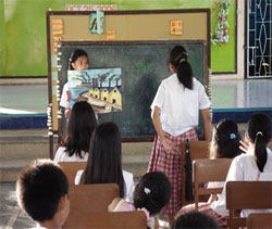 Image of two girls in the Philippines giving a presentation on the environment