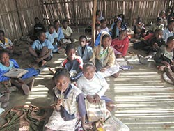 Interior of slat-walled classroom with children sitting on floor with school books.