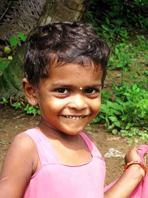 Photo of preschool-age girl from India, smiling.