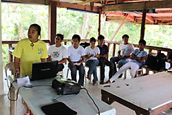 In the Philippines, a group of EcoScouts talk through their website, which is projected up on a screen.