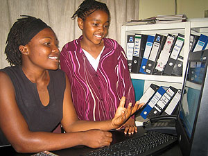 Young woman, seated at a computer, talking to a younger girl.