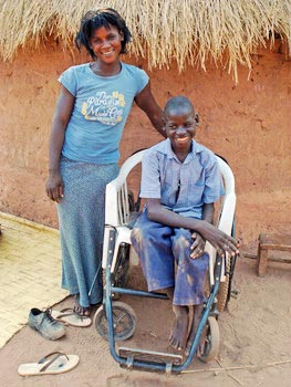 Woman standing, boy in wheelchair, both smiling