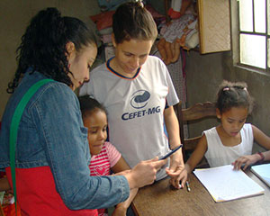 Woman shows tablet computer to two children; a child sits at a table next to them, with stationery.