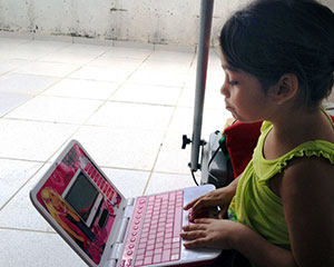 Young girl with small pink laptop.