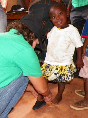 ChildFund staff person placing shoes on a young girl's foot.