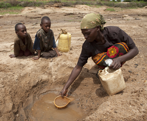 Woman draws water from muddy pit while two girls look on.