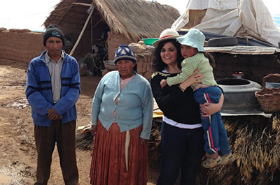 Caroline, of France, meets her sponsored child María and her family at María's home in La Paz, Bolivia.