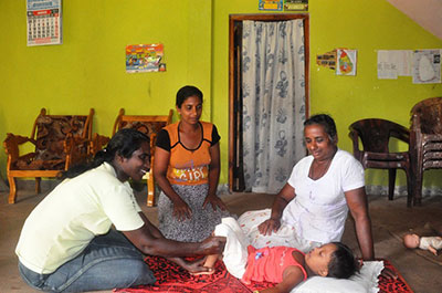 Anoma, a volunteer with one of ChildFund's local partners in Sri Lanka, does exercises with Umesha while her mother and grandmother look on.