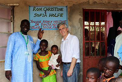 Ron Wolfe, a ChildFund staff member, visiting with his 11-year-old sponsored child and her family in The Gambia.