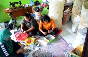 Indonesian mothers sort through garbage