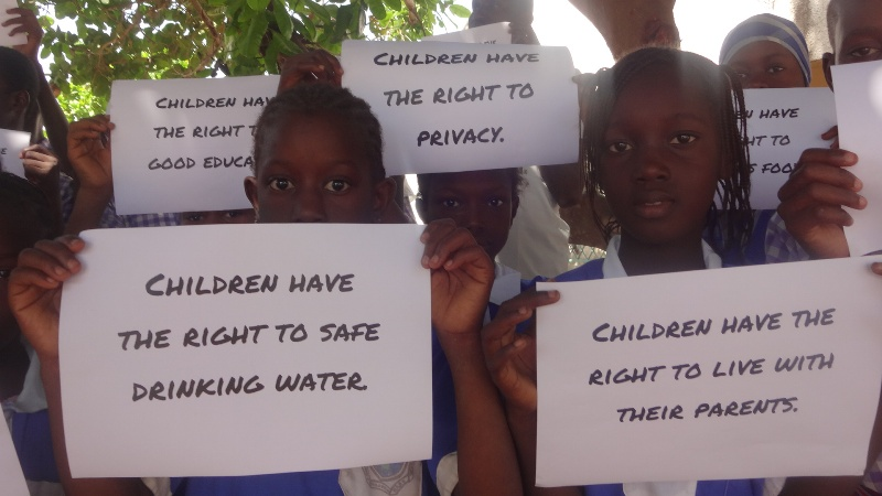 Children hold signs displaying their many rights.