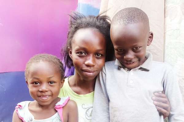 Catherine hugs her children Akinyi, 5 and Ochieng, 7, at their home in Dandora, Kenya.