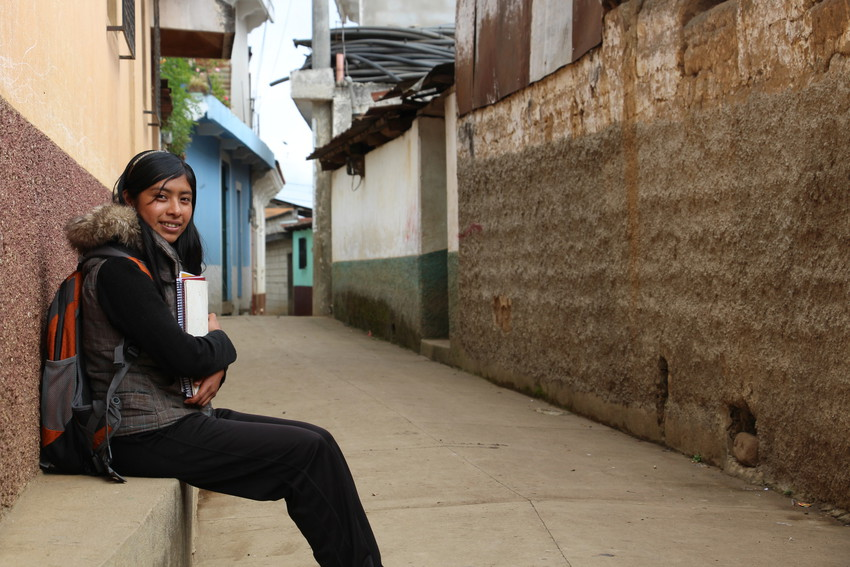 Schoolgirl in Guatemala sits outside in a empty street wearing backpack and holding books, smiling.
