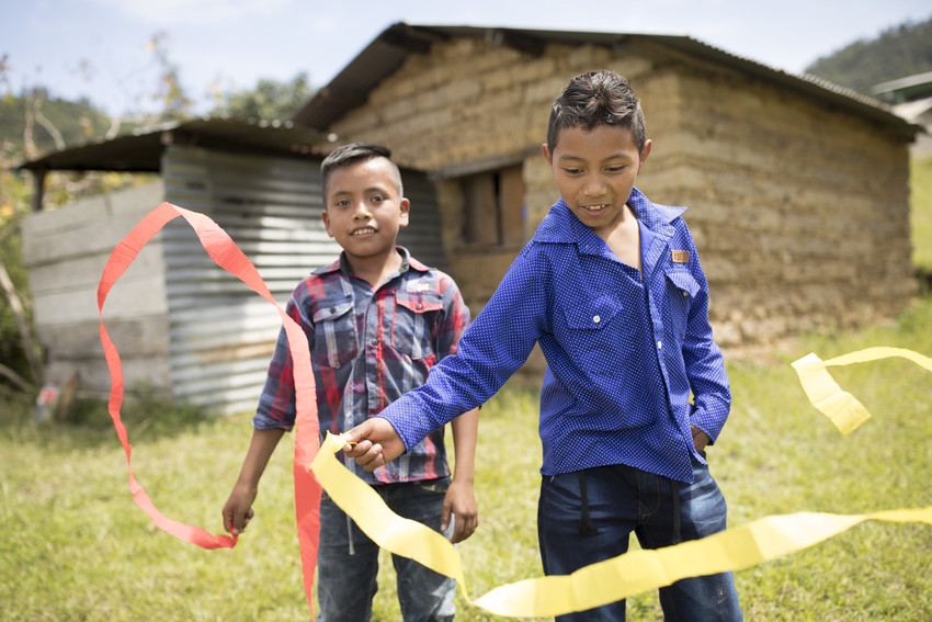 Two boys standing outside in Guatemala playing, waving red and yellow streamers in the air.