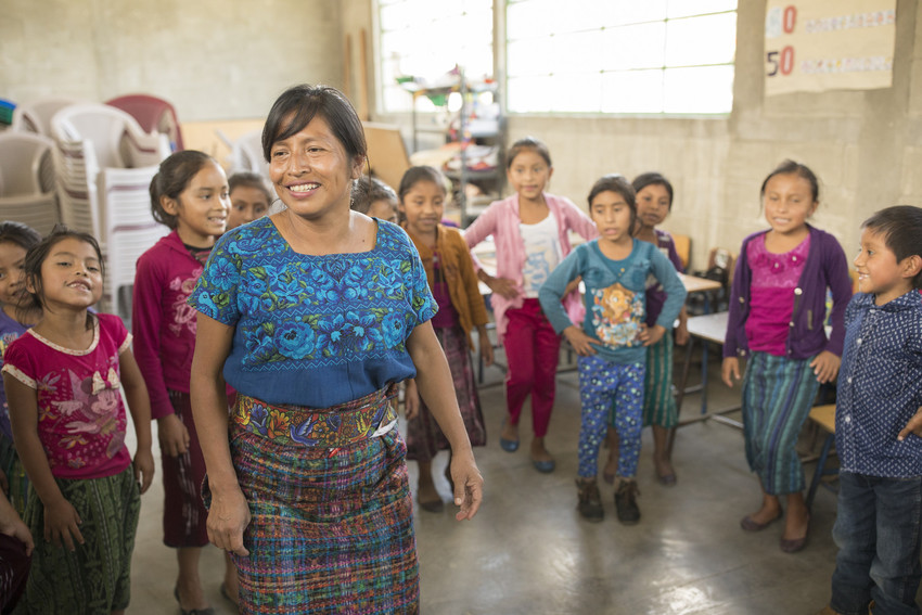 A teacher in a blue traditional Guatemalan dress stands in room full of elementary students at school, smiling.