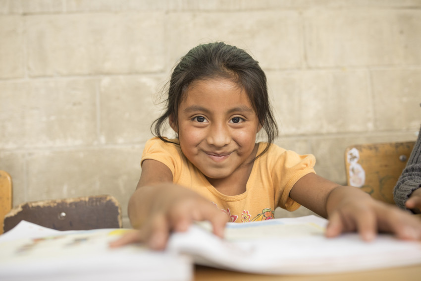 Young girl sits at a desk at school in Guatemala, holding papers, smiling.
