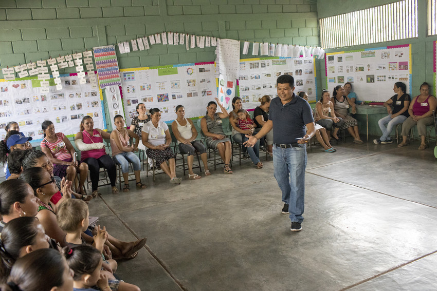 Male teacher at school in Guatemala stands in the middle of a classroom full of parents, talking and gesturing with his hands.