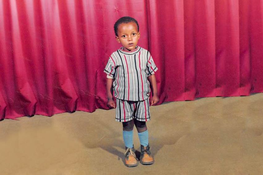 Boy child standing in front of red curtain in Ethiopia.