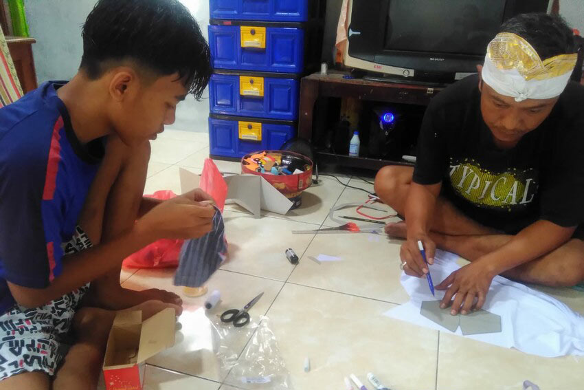 Boy and father sit inside making facemasks in Indonesia.