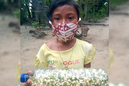 Girl wearing facemask stands outdoors holding bottle filled with sprouts in Indonesia.