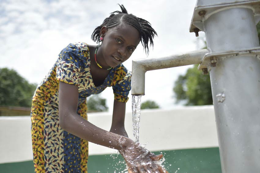Girl washes hands at water well outside smiling in Sierra Leone.