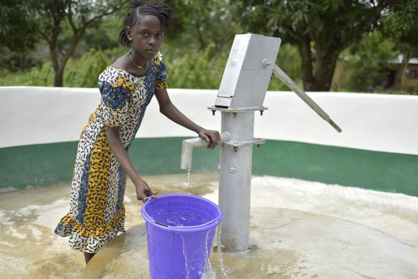 Girl stands outside at water pump well with blue bucket in Sierra Leone.