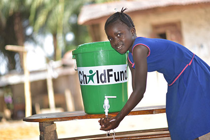 A 10-year-old girl in Sierra Leone washes her hands with water from a green bucket labeled ChildFund.