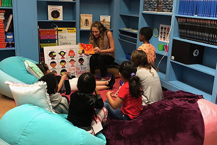 A woman reads a story to a group of children sitting in bean bags in a brightly colored classroom corner in the United States.