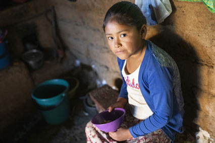 Girl in Bolivia sits inside holding empty bowl.