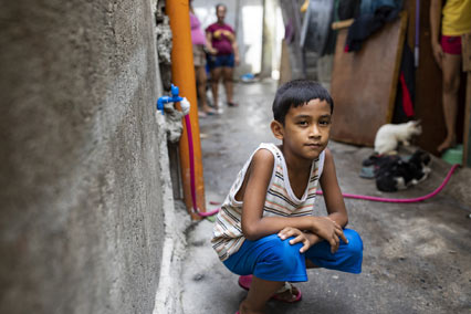 Boy in Philippines squatting in alleyway.