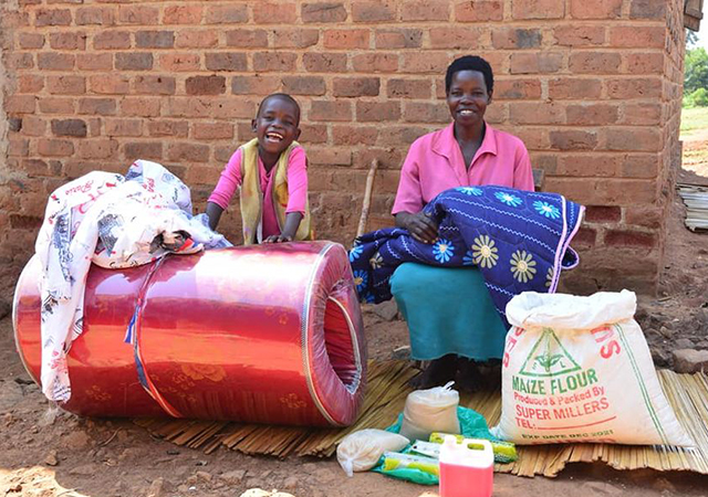 Yofisa and his mother celebrate the gifts in kind received with the help of donors and ChildFund resources.