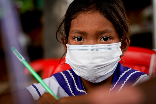 Girl in Cambodia sits at a desk wearing a mask, looking at camera