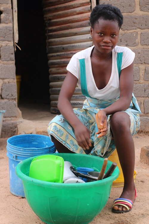 Teenage girl in Zambia washes dishes while looking at camera.