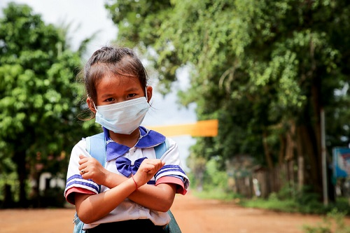 Girl in Cambodia stands looking at camera wearing mask