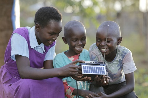 Girl and her siblings in Kenya sit around a radio, smiling