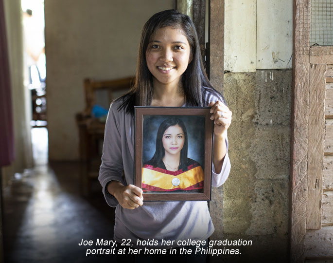 portrait of girl, woman standing inside holding photograph of herself in Philippines