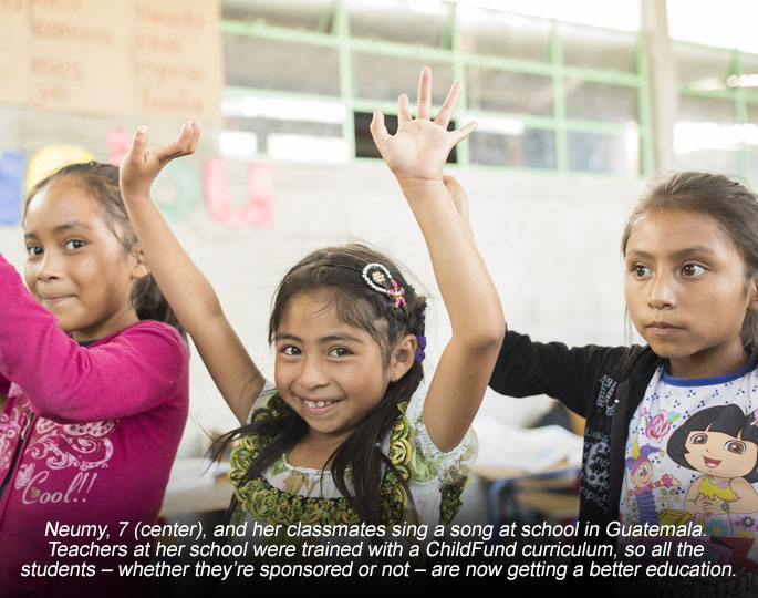 Three girls with their arms up in a classroom in school in Guatemala.