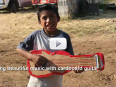 Screenshot of video depicting boy playing cardboard guitar