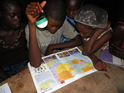 Children in Liberia use a hand-held solar light to study.