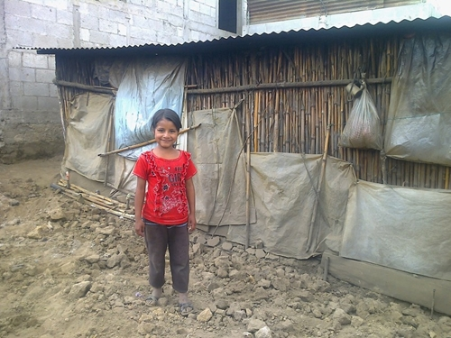Maria stands outside of her home after an earthquake in Guatemala.