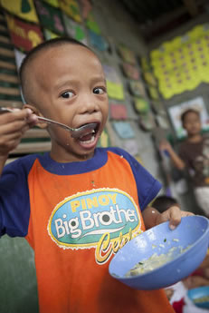 Image of a little boy eating a meal at the ChildFund Supervised Neighborhood Play center in Pili, Philippines