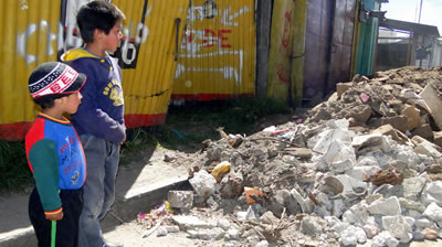 Children observe destroyed homes in Guatemala, which suffered a massive earthquake in November 2012.