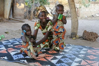 Senegal, mother with twin daughters