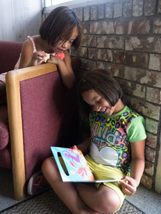 Two girls in Oklahoma who are part of ChildFund's Just Read! program enjoy looking at a book.