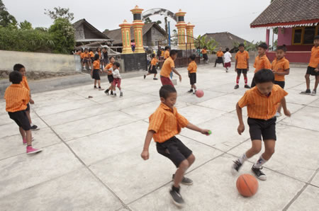 Image of children playing soccer at a primary school in Indonesia