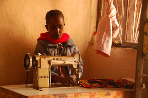 Tigist sews traditional dresses at her sewing machine provided by ChildFund.