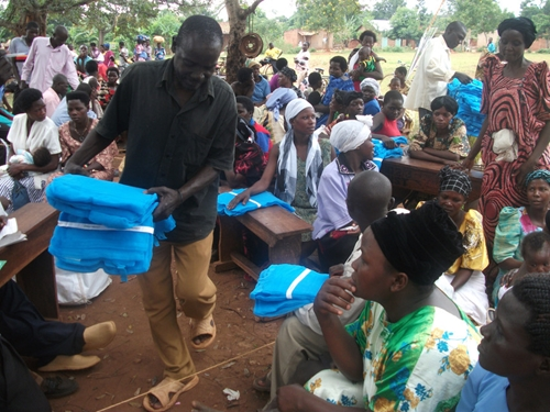 Mosquito nets for beds are distributed to families in Uganda.